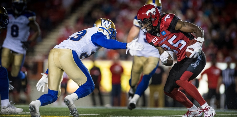 Kevin Fogg (23) of the Winnipeg Blue Bombers and Joe West (85) of the Calgary Stampeders during the game at McMahon stadium in Calgary, AB. Friday, July 1, 2016.  (Photo: Johany Jutras)