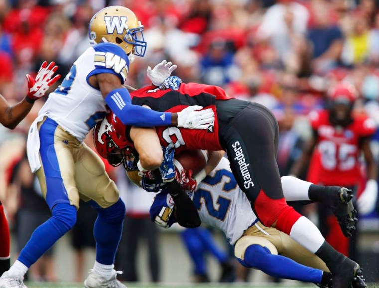 Calgary Stampeders' Rob Cote is tackled by Winnipeg Blue Bombers' Bruce Johnson, bottom, and Julian Posey during first quarter CFL football action in Calgary, Friday, July 1, 2016.THE CANADIAN PRESS/Jeff McIntosh