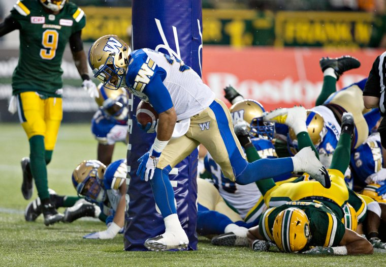 Winnipeg Blue Bombers Andrew Harris (33) runs in for a touchdown against the Edmonton Eskimos during first half CFL action in Edmonton, Alta., on Thursday July 28, 2016. THE CANADIAN PRESS/Jason Franson.