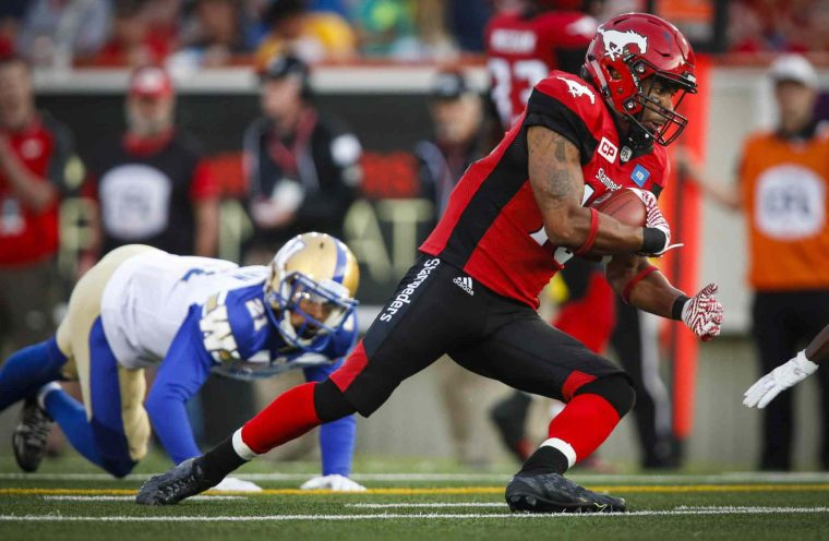 Winnipeg Blue Bombers' Brendan Morgan, left, looks on as Calgary Stampeders' Jerome Messam runs the ball during first half CFL football action in Calgary, Friday, July 1, 2016.THE CANADIAN PRESS/Jeff McIntosh