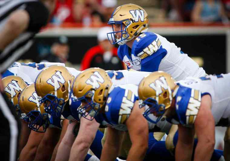 Winnipeg Blue Bombers' quarterback Matt Nichols, top, calls the play during first half CFL football action against the Calgary Stampeders in Calgary, Friday, July 1, 2016.THE CANADIAN PRESS/Jeff McIntosh. I DO NOT OWN THIS PHOTO OR CLAIM TO.